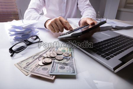 businessman using calculator with dollar currency