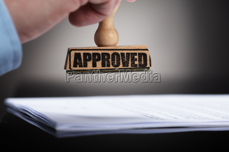 businessperson stamping on approved contract form