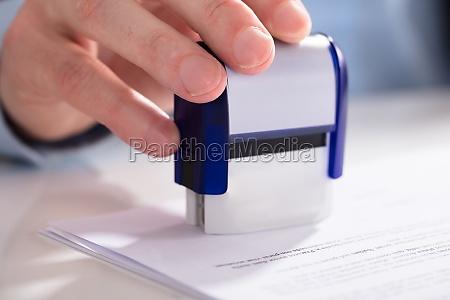businessperson using stamper on document