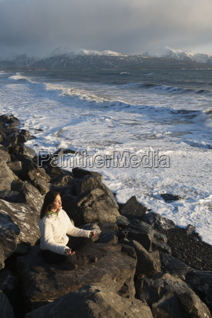 woman practicing meditation on a rocky