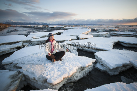 woman practicing meditation on ice chunks
