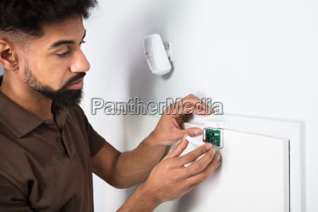 technician fixing security system door sensor