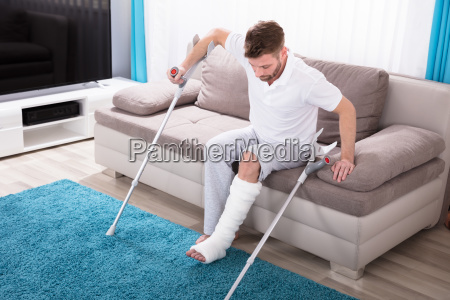 man with broken leg getting up