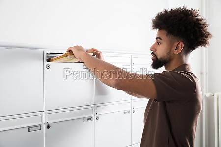 mann der buchstaben in mailbox einsetzt