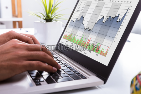 boersenmakler analysiert grafik am laptop