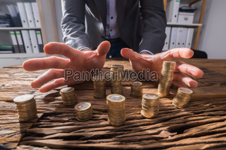 businesspersons hand surrounding stack of coins