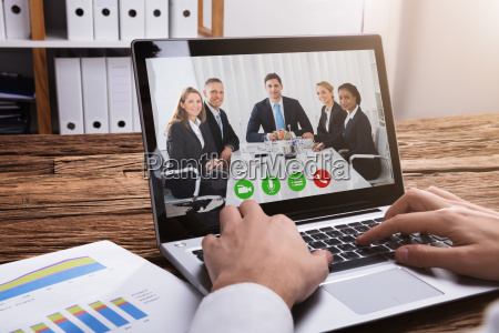 businessperson video conferencing with colleagues on