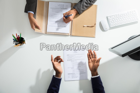 businessperson and candidates hand over white