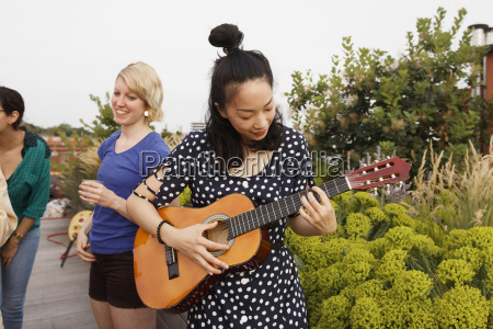 young woman playing guitar on patio