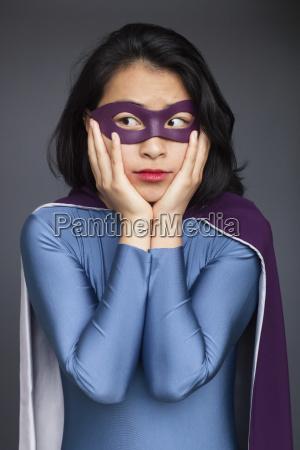 young woman wearing superhero costume standing