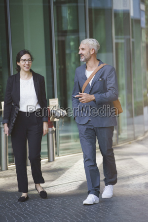 happy business people talking while walking
