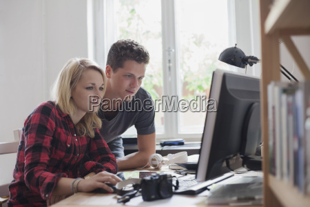 young couple using computer against window