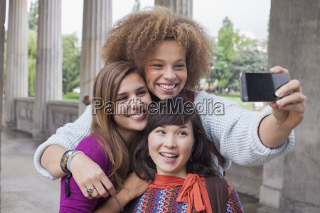 smiling young woman taking selfie with