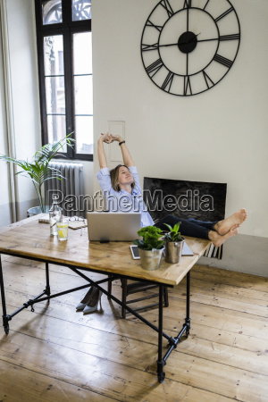 relaxed woman sitting at desk at