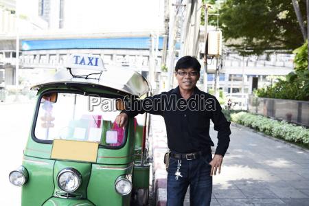 thailand bangkok tuk tuk driver standing