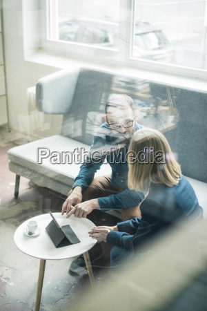 businessman and businesswoman with tablet discussing