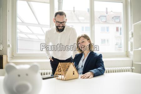 lachende frau und mann mit hausmodell