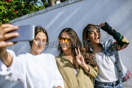drei laechelnde junge frauen nehmen selfie