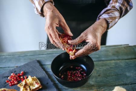 mans hands peeling a pomegranate
