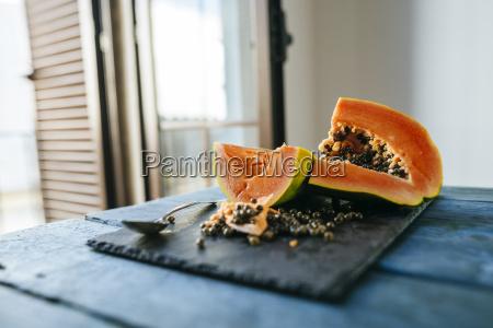 papaya geschnitten auf schiefer auf blauem