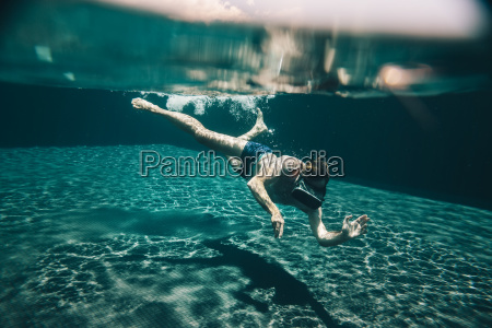 man diving in a swimming pool