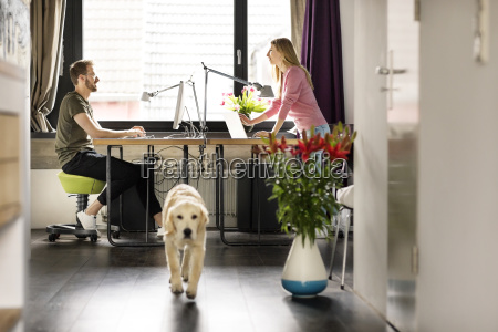 man and woman with dog working