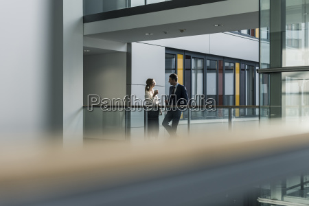 businessman and businesswoman talking on office