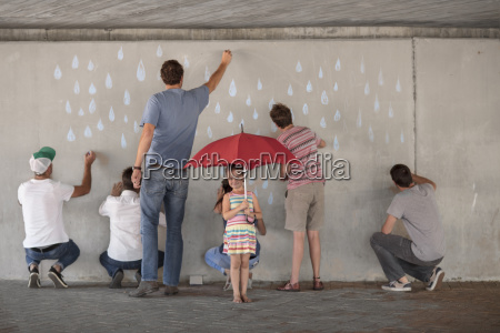 people drawing raindrops on concrete wall
