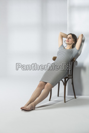 young woman reclining on chair against