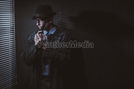 junger mann steht mit pistole per