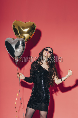 happy young woman holding helium balloons