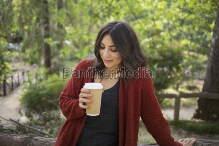 mid adult woman holding disposable glass