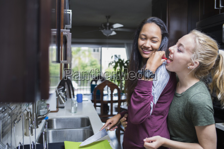 happy woman feeding another woman fruit