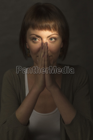 mid adult woman meditating with hands