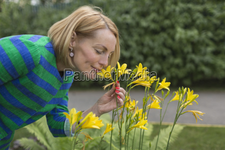side view of mature woman smelling