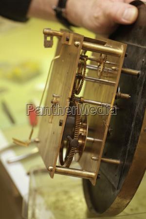 uhrmacher restauriert alte wanduhr
