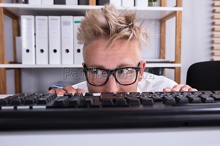 funny businessman hiding behind desk