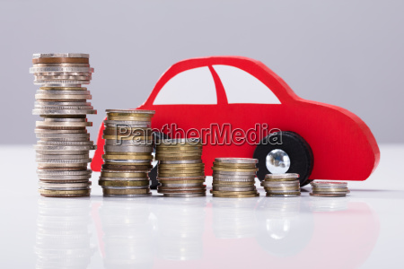 red car over stacked coins