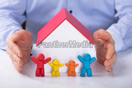 hand protecting the house model with