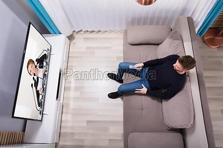man watching television at home