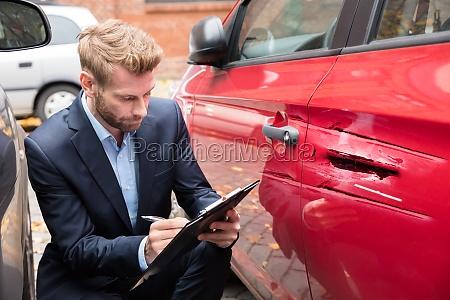 versicherungsmakler prueft auto nach unfall