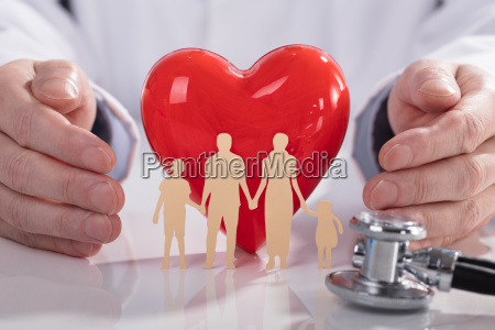 doctor protecting red heart and family