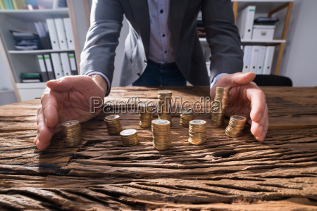 businessperson protecting stacked coins