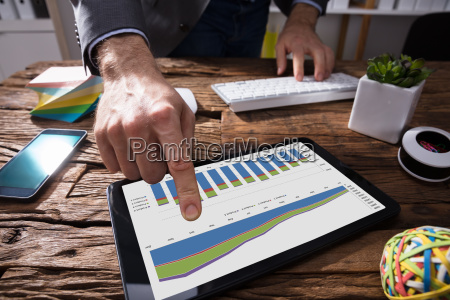businessperson using digital tablet with graph