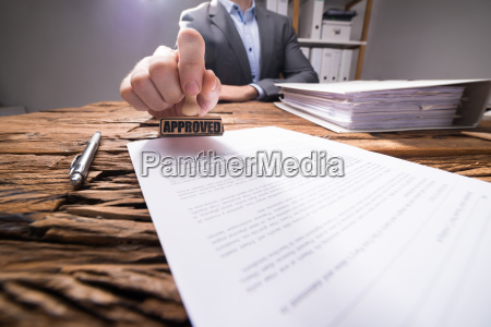 nahaufnahme eines wirtschaftlers der dokument genehmigt