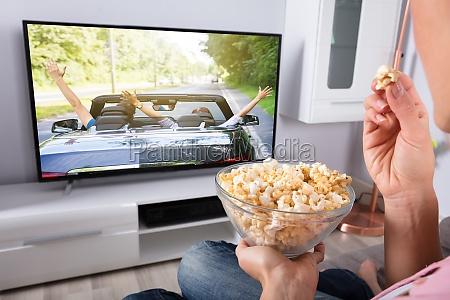 die hand der person die popcorn