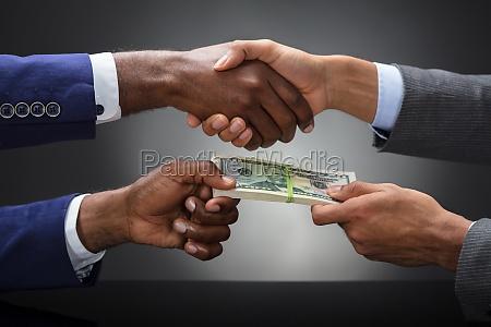 businessman shaking hands while bribing partner