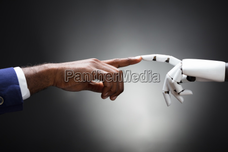 fingers of robot and man touching