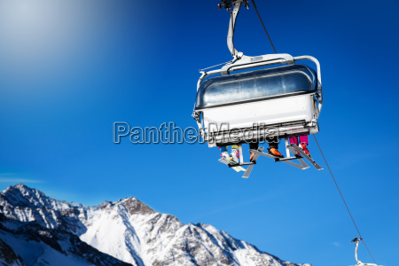 skiers in a chairlift against blue