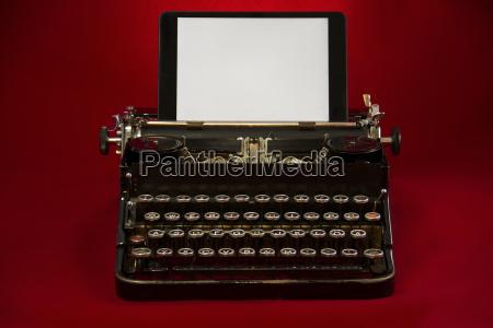 nostalgic typewriter with tablet